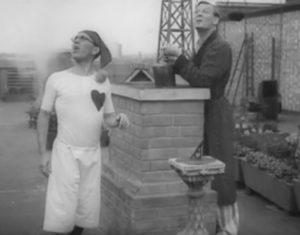 Standing on either side of a chimney, Arthur Askey (in long white shorts, a white t-shirt with a heart on it and wearing a stocking cap) and Stinker Murdoch (in pajamas and dressing gown) look up.