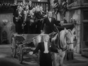 "In white-tie and tails, Jack Hylton leads his band, who ride on the literal ""band waggon"", complete with a tympanist on the horse pulling it."