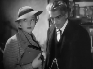 In a wide-brimmed hat, Clare (Anna Lee) looks to the side while Laurience (Boris Karloff) stares into space with one cocked eyebrow.
