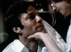 Fitzgerald (Rchard Chamberlain) looks up at Zelda (Blythe Danner), who holds his chin in her hand as she wipes blood from his face with a cloth.