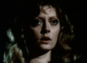 At night, with wavy brown hair, Ailie (Susan Sarandon) stares with large eyes and her mouth slightly open.