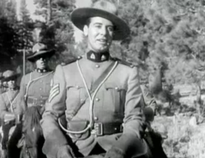 In uniform , Sergeant Renfrew (James Newill) sings as he rides his horse.