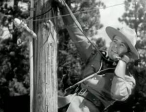 Renfrew (James Newill) talks on a telephone while up a telephone pole.