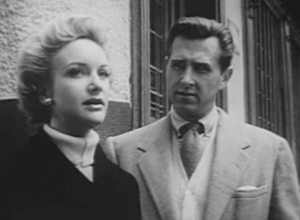 Outside a building, Frank (Lloyd Bridges) watches Pauline (Moira Lister) talk as he looks warily in another direction.