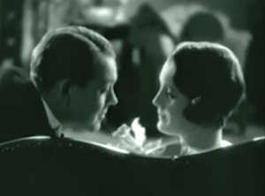 Jim (Robert Ames) and Mary (Mary Astor) face each other on a sofa.