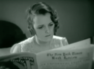 Sitting up in bed in pajamas, Mary (Mary Astor) bites her lip as she reads The New York Times Book Review.