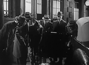 Outside the police station, several men - detectives and reporters - look down at a body next to a car.