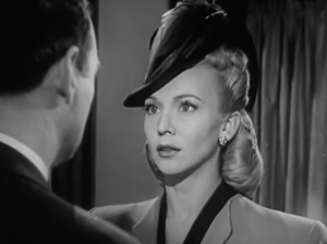 Blonde and wearing a fashionable hat, Janet (Carole Landis) stares at Sam (William Gargan).