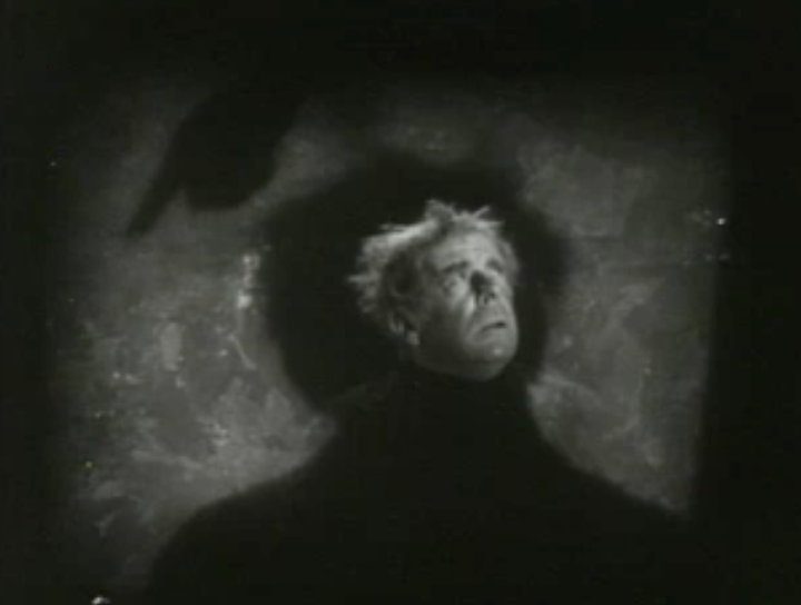 His head surrounded by his own shadow against a wall, Scrooge (Seymour Hicks) looks up at a ghost whose shadow finger points down.