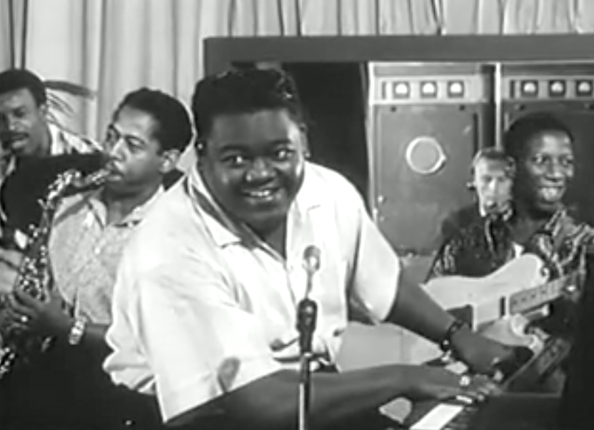 Wearing a short-sleeved white shirt and a square haircut, Fats Domino smiles as he plays piano, performing with his band.