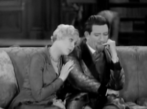 On a sofa, Madeline (Esther Ralston) rests her head on Richard's (Edward Everett Horton) shoulder as he bites his fingernail.