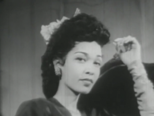 Gertie (Francine Everett) stares at the camera, unsmiling, her raised hand wearing opera-length gloves.