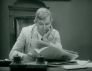 Judge Priest (Will Rogers) reads a newspaper while presiding in his courtroom.