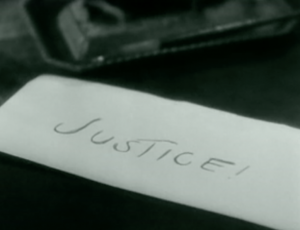 "The word ""JUSTICE!"" is written on an envelope."